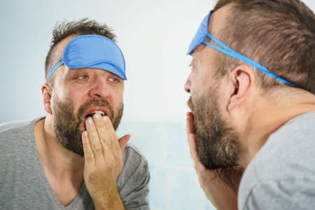 Funny adult man wearing eyemask on forhead having troubles with waking up. Standing in front of mirror looking at his face, yawning, being tired and sleepy. 写真素材
