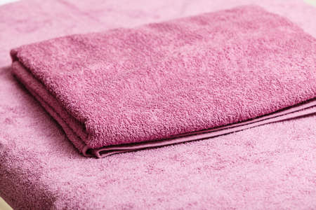 Household bathroom equipment, water absorption concept. Detailed closeup of pink microfiber towel