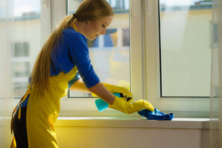 Young woman cleaning windowsill using blue cloth and detergent. Household duties concept. Banque d'images
