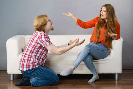 Man begging woman who is sitting on sofa for forgiveness. Couple after fight or argue.