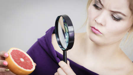 Blonde woman holding magnifying glass investigating and looking closely fruit orange or grapefruit