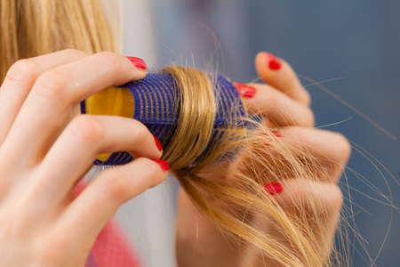 Frau, die ihr Haar mit Rollen kräuselt Standard-Bild