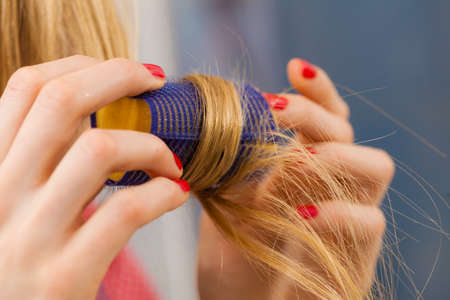 Woman curling her hair using rollers Imagens