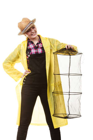 Spinning, angling, cheerful fisherwoman concept. Happy woman in yellow raincoat holding empty fishing keepnet, having fun.