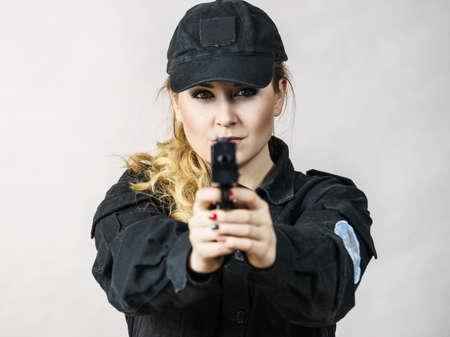 Glückliche junge Frau, die Polizist ist, der Waffe hält und damit zeigt.