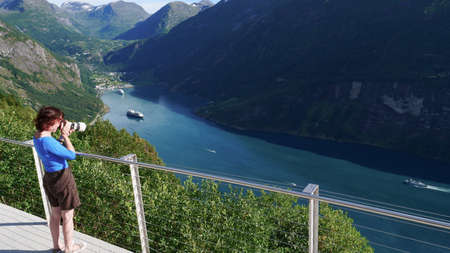 Tourism holidays pictures and traveling. Mature female tourist enjoying scenic fjord landscape Geirangerfjord from Ornesvingen viewpoint, taking photo with camera, Norway Scandinavia.