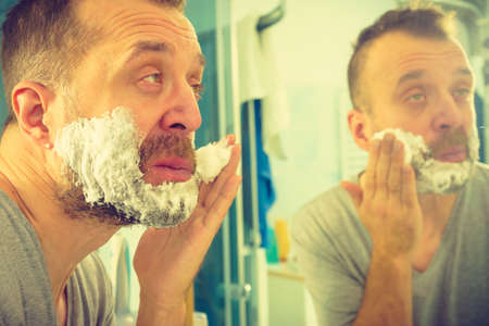 Man applying shaving foam cream on his face, standing in bathroom, looking at mirror, preparing to shave his face beard. Skincare Stock fotó