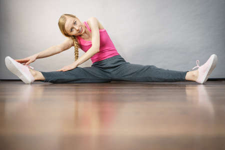 Young blonde woman in sportswear sitting on wooden floor indoor stretching legs. Training at home, being fit and healthy.