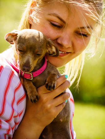 Woman playing with little pinscher ratter prazsky krysarik crossbreed hugging small dog outside on grass during summer spring weather