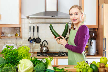 Woman in kitchen with many green leafy vegetables, fresh organically produce on counter. Young happy housewife holding marrow zucchini in hands. Healthy eating, cooking, vegetarian food, dieting and people concept. Фото со стока - 111661852