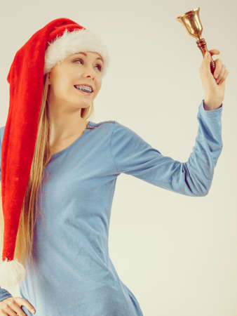 Happy positive young teenage woman wearing Santa Claus christmas hat holding decorative old fashioned bell. Stock Photo