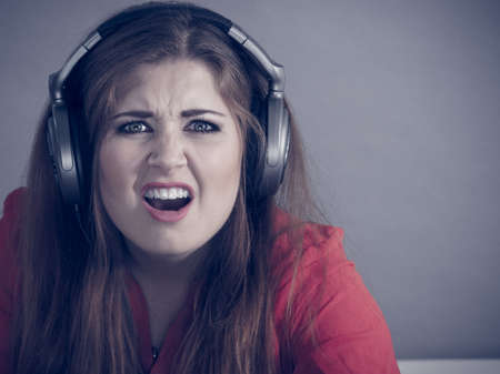 Grumpy young woman wearing gaming headphones having complaining face expression seeing something unpleasant