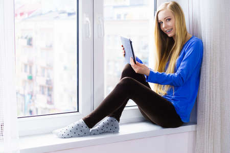 Technology internet, digital online learning concept. Smiling long hair teen girl dental braces on her teeth using tablet pc computer sitting on window sill.