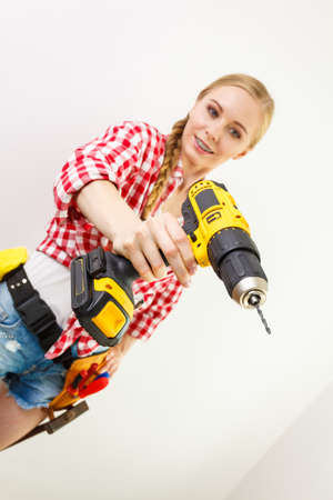 Young determinated woman using drill doing home renovation. Female construction worker having driller tool drilling wall.