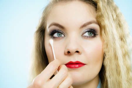 Professional artist fixing fashion model make up using ear buds cotton tipped swabs q tip