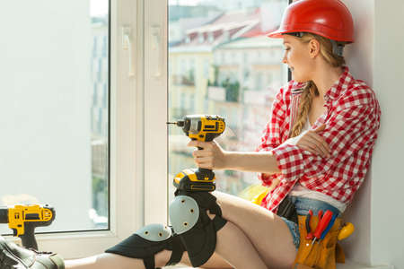 Pretty young woman construction worker with helmet about to fix window picking best tools. Working at flat remodeling. Building, repair and renovation. Stock Photo