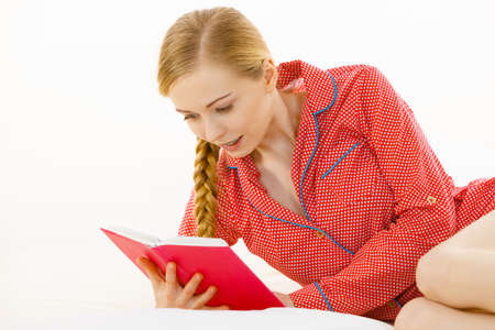 Girl lying in bed reading book. Young blonde female wearing red dotted pajamas relaxing at home on mattress. Imagens