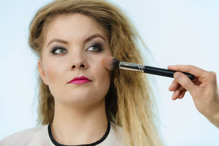 Make up and beauty. Makeup artist applying with brush powder rouge on female check 写真素材