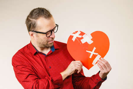 Bad relationships, breaking up, sadness emotions concept. Adult man holding broken heart, on grey Stockfoto