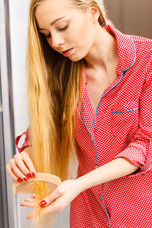 Woman combing brushing her long smooth hair in bathroom with wooden comb. Girl taking care refreshing her hairstyle. Haircare concept.
