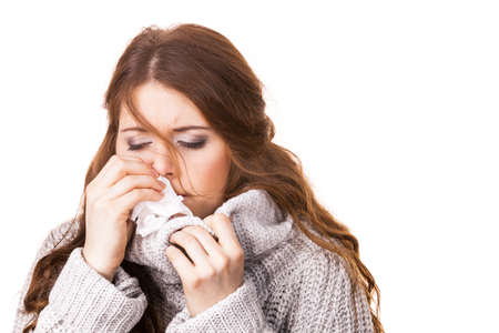Sick freezing woman sneezing in tissue. Girl wearing warm sweater being cold and trembling. Flu or other virus. Health care. 스톡 콘텐츠