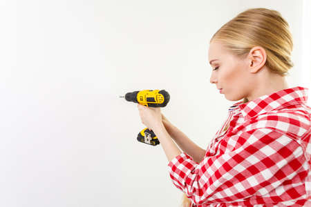 Young determinated woman using drill doing home renovation.