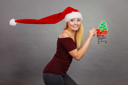 Xmas, seasonal sales, winter celebration concept. Happy woman wearing Santa Claus helper hat holding shopping basket cart with little christmas tree and gifts inside running for sale.