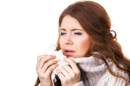 Sick freezing woman sneezing in tissue. Girl wearing warm sweater being cold and trembling. Flu or other virus. Health care. 版權商用圖片