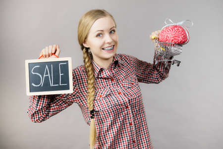 Happy woman holding shopping cart with brain inside and sale sign. Clever, responsible buying concept.