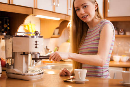 Woman in kitchen making hot drink coffee from machine. Barista at home. Banque d'images