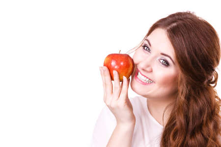 Woman holding red apple fruit in hand close to face, smiling, isolated on white. Healthy eating, high fibre diet concept. 免版税图像