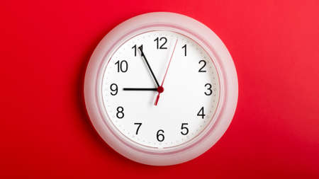 White clock hanging on red wall showing nine hours.