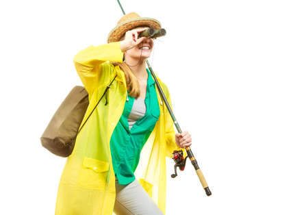 Fishery, spinning equipment, angling sport, activity concept. Woman wearing raincoat holding fishing rod and binoculars, ready for adventure. Banque d'images