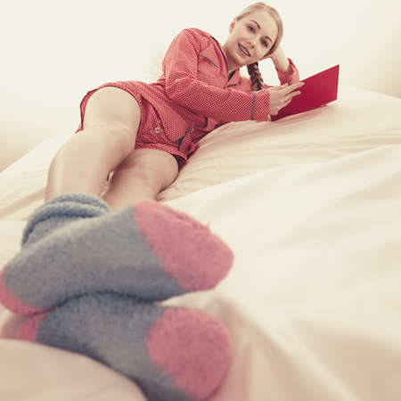 Girl lying in bed reading book. Young blonde female wearing red dotted pajamas blue warm socks relaxing at home on mattress. Stockfoto - 112736976