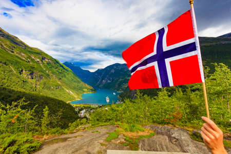Norwegian flag and beautiful view over Geirangerfjorden from Flydalsjuvet viewing point. Tourist attraction. Tourism vacation and travel. 免版税图像