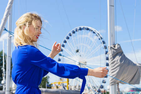 Fashionable woman wearing blue jumpsuit shorts perfect for summer. Fashion model outdoor photo shoot posing against ferris wheel Banco de Imagens