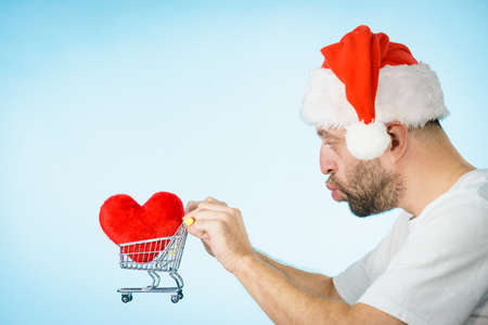 Man wearing santa hat holding shopping basket cart with red heart, side view on blue. Christmas, charity sharing concept. Stock Photo