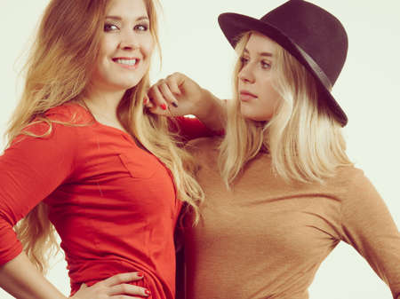 Two fashionable pretty women wearing beautiful stylish outfits. One wearing suede dress and sun hat, friend long sleeve red top. Фото со стока