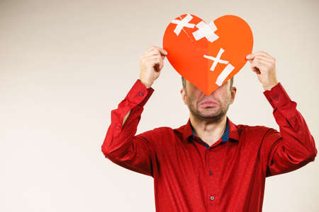 Bad relationships, breaking up, sadness emotions concept. Adult man holding broken heart, covering his face, on grey Stock Photo