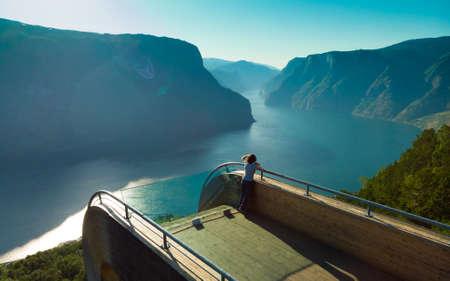 Tourist woman enjoying fjord view Aurlandsfjord landscape from Stegastein viewing point. Norway Scandinavia. National tourist route Aurlandsfjellet.