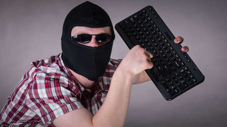 Crazy hacker man. Unrecognizable guy wearing black balaclava holding computer keyboard. Hate speech on the internet. Stok Fotoğraf