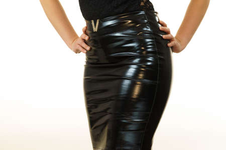 Unrecognizable woman wearing all black outfit, leather latex dark tight skirt showing her hips body curves.