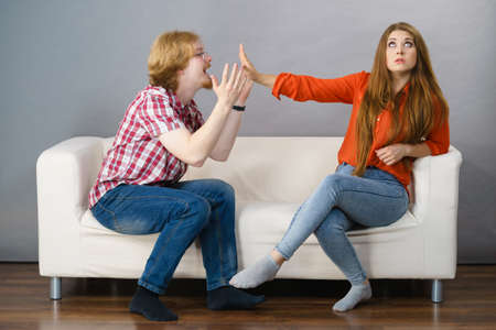 Man begging woman who is sitting on sofa for forgiveness. Couple after fight or argue. Female showing speak to hand
