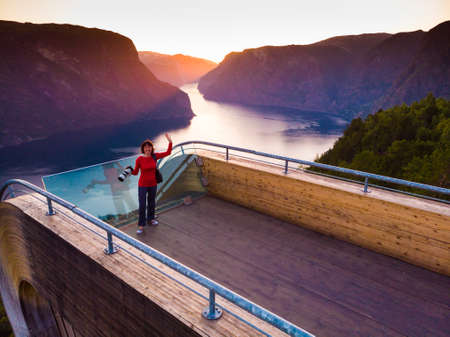 Aerial view. Tourist woman with camera enjoying fjord view Aurlandsfjord landscape from Stegastein viewing point. Norway Scandinavia. National tourist route Aurlandsfjellet. Stock Photo