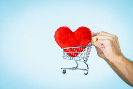 Male hands holding shopping basket cart with red heart. Love, valentines day, charity sharing concept. Stock Photo