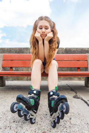 Sad funny teenage woman wearing roller skates. Frustrated female waiting for somebody while sitting on bench outdoor.