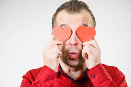 Adult funny man covering eyes with red hearts. Male blinded by love. Romance feelings valentines day concept