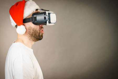 Man wearing santa claus hat exploring space with virtual reality goggles headset, vr box. Cyber christmas concept, on grey, side view with copy space Stockfoto