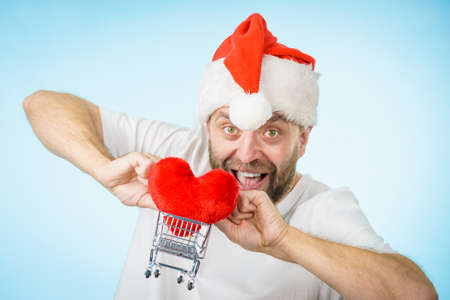Man wearing santa hat holding shopping basket cart with red heart, on blue. Christmas, charity sharing concept. Stock Photo