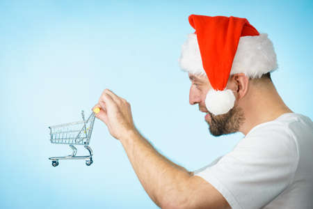 Man wearing santa claus hat holding empty shopping basket cart, on blue. Xmas, seasonal sales, boxing day concept. Stock Photo